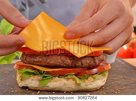 Cheddar cheese on burger.Preparing and making hamburger.
