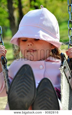 Pretty toddler girl riding on swing