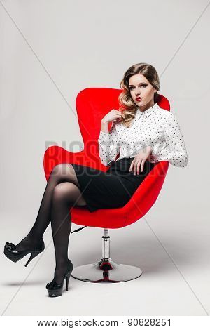 beautiful girl with curly hair in shirt and black skirt on white background red chair