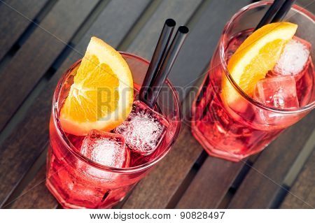 Close-up Of View Of Glasses Of Spritz Aperitif Aperol Red Cocktail With Orange Slices And Ice Cubes