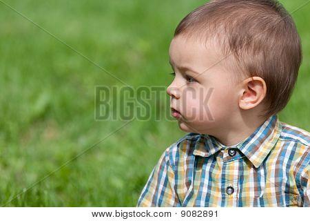 Closeup Retrato de un niño pensativo contra la hierba verde