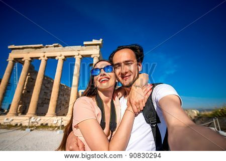 Young couple taking selfie picture with Erechtheum temple on background in Acropolis