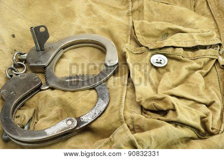 Handcuffs, Security Concept On  Camouflage Backpack Background