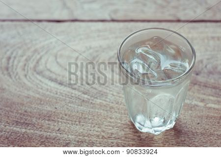 Drinking Water With Ice In Glass On Wooden Table