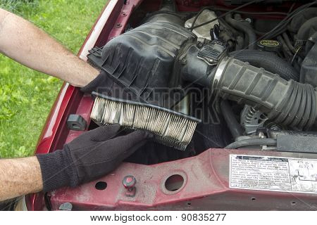 A Mechanic Replacing A Dirty Air Filter In A Truck