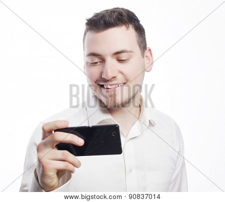 business,tehnology and people concept - Handsome happy business man reading an SMS on smartphone against white background