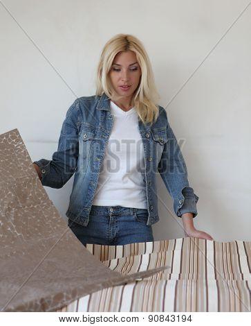 Beautiful young woman chooses wallpaper