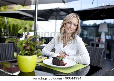 Very beautiful young woman, sit in Cafe and eating cake