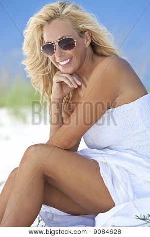 Beautiful Blond Woman In White Dress And Sunglasses At Beach