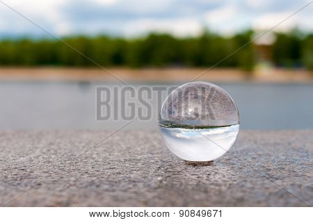 Glass transparent ball on river background and grainy surface. With empty space