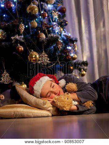 A boy sleeps under the Christmas tree