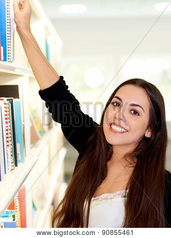 Happy Friendly Young Woman Reaching For A Book