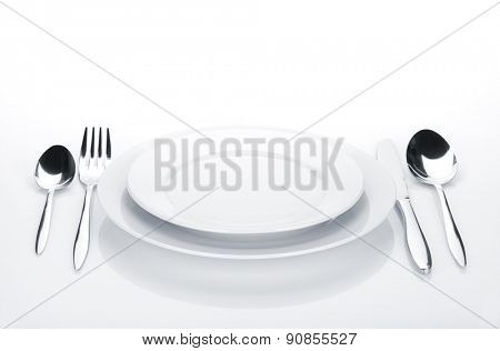 Silverware or flatware set and plates. Isolated on white background