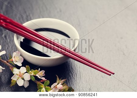 Japanese sushi chopsticks, soy sauce bowl and sakura blossom on black stone background. Top view with copy space. Toned
