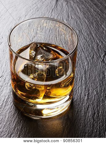 Glass of scotch whiskey with ice on black stone table