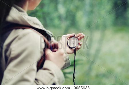 Woman Discovering Nature And Checking Directions With Compass In The Mountains
