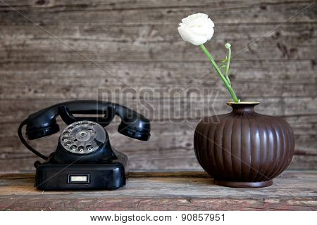 Rotary Telephone Next To A White Carnation Flower