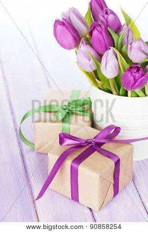 Purple tulip bouquet and gift boxes on wooden table