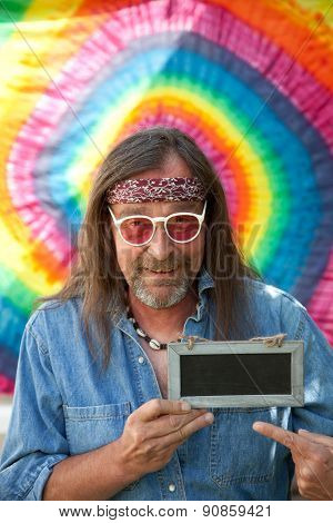 Hippie Man Pointing Towards A Blank Blackboard