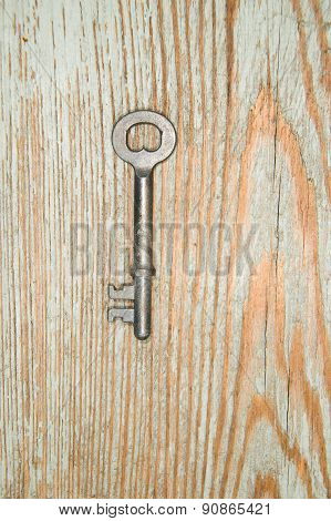 Old Key From The Lock On A Wooden Texture