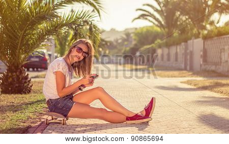 Young girl with skateboard and smartphone sitting outdoors on summer