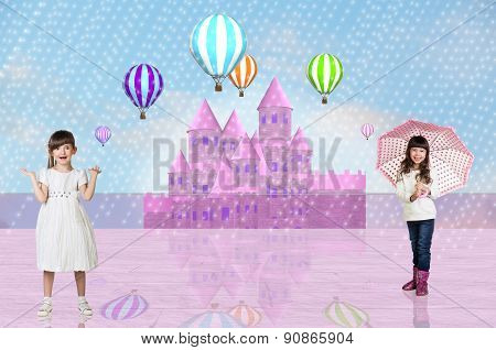 Two little girls in front of a pink fairy castle