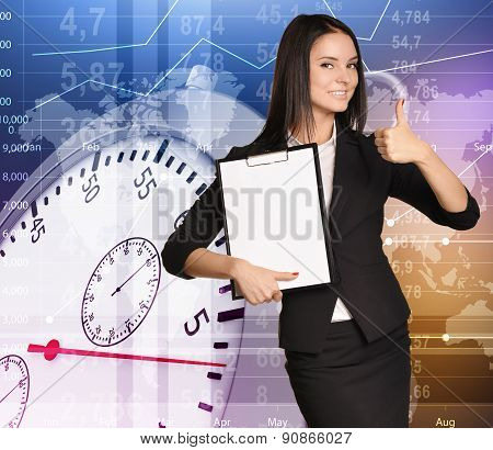 Young girl stands on background stopwatch holding clipboard and showing sign thumb up