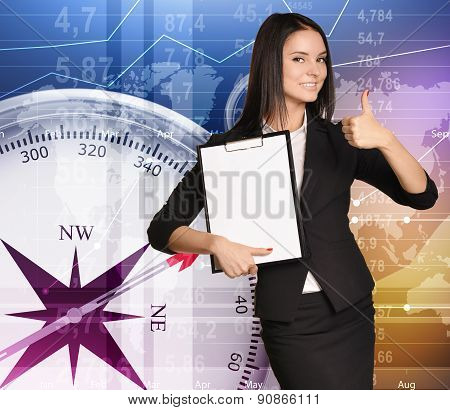 Girl stands on background compass holding clipboard and showing sign thumb up