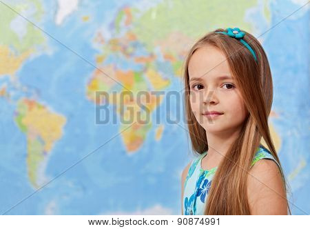 Young girl in front of world map - in geography class, with copy space