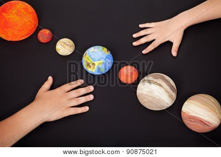 Kids hands with the planets of the solar system - science home project, focus on Earth