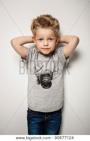 Little pretty boy posing at studio as a fashion model