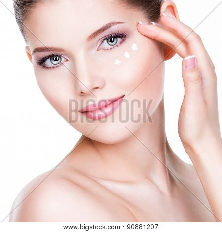 Closeup portrait of young woman applying cream on her pretty face - on a white background.