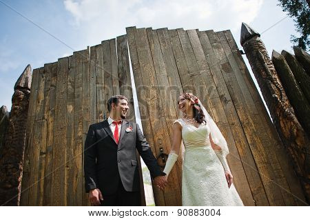 Wedding Couple Near Old Wooden Fence Holding Hands