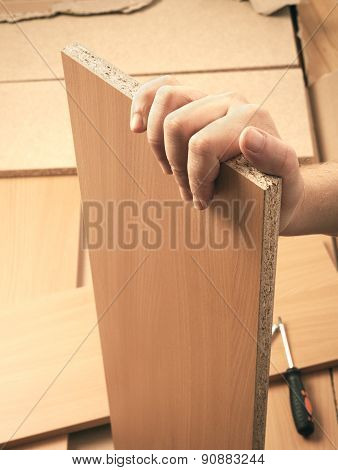 Carpenter hand holding plank and mounting brown wooden furniture