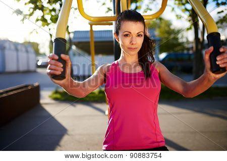 Woman Using Weight Machine Outside.