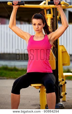 Muscular Woman Sitting On Weights Machine Exercising Arms.