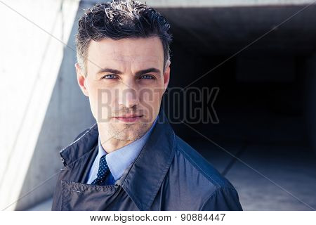 Portrait of a confident businessman standing outdoors and looking at camera