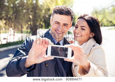 Smiling couple making selfie photo on smartphone in park