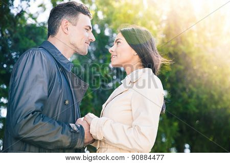 Portrait of a beautiful couple flirting in park and looking at each other