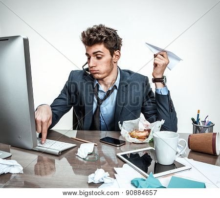 Young Office Man With Paper Plane In His Hand Typing On A Computer Keyboard / Modern Office Man At W