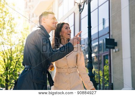 Smiling handsome man pointing on something to his happy wife outdoors