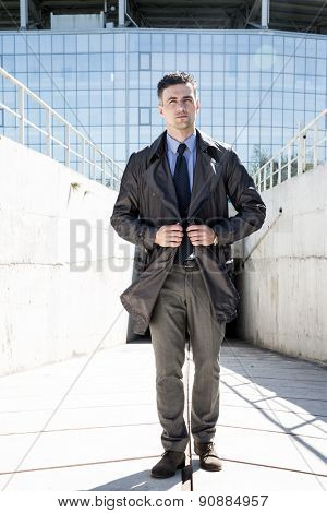 Full length portrait of a handsome businessman standing outdoors
