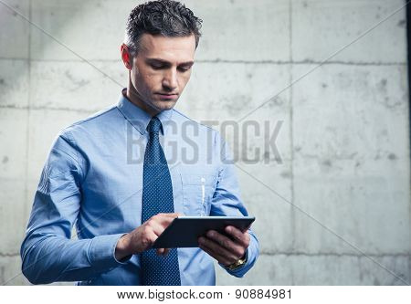 Serious businessman standing and using tablet computer over concrete wall