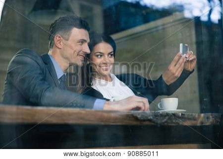 Smiling businesswoman and businessman making selfie photo on smartphone in cafe