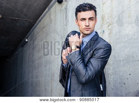 Portrait of a handsome businessman standing over concrete wall