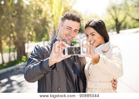 Happy couple making selfie photo on smartphone outdoors