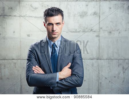 Portrait of a confident businessman standing with arms folded over concrete wall