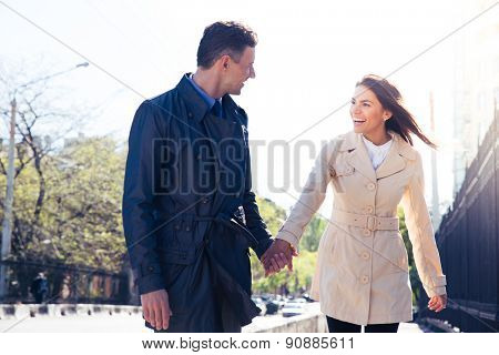 Laughing young couple walking and flirting outdoors