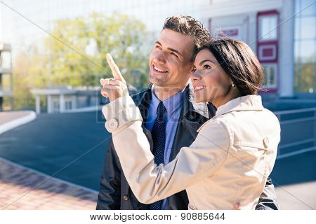 Happy woman pointing to something to her husband outdoors