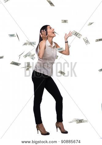 Full length portrait of a businesswoman under money rain isolated on a white background